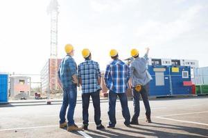 gruppo di costruttori in elmetti protettivi all'aperto foto