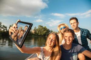 amici allegri che prendono selfie su una barca foto