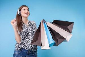 la giovane donna allegra con le cuffie sta comprando i vestiti foto