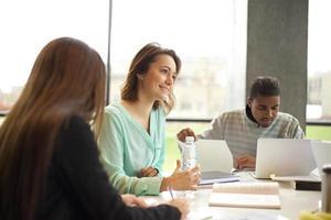 giovane donna che studia in biblioteca con altri studenti