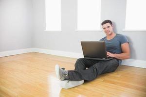 uomo bello allegro che si appoggia contro la parete per mezzo del computer portatile foto
