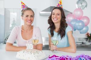 donne allegre che bevono vino bianco e festeggiano il compleanno foto