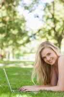 Ritratto di giovane donna allegra che per mezzo del suo computer portatile foto