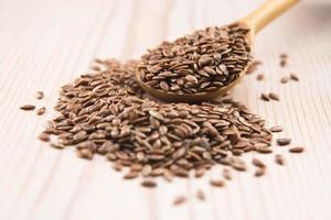 olio di semi di lino e semi di lino su fondo di legno foto