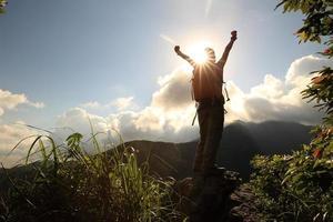 Viandante incoraggiante della donna a braccia aperte alla scogliera del picco di montagna foto