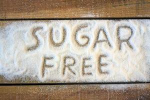 senza zucchero scritto su zucchero bianco su una superficie di legno foto