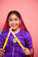 bella ragazza adolescente indiana attraente allegra che tiene bastoni dandiya