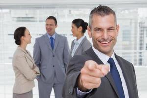 uomo d'affari allegro che indica alla macchina fotografica con i colleghi su backgr foto