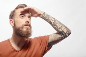 bell'uomo barbuto con la mano in testa foto