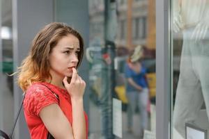 ragazza in una camicia rossa in piedi pensieroso vicino al negozio foto