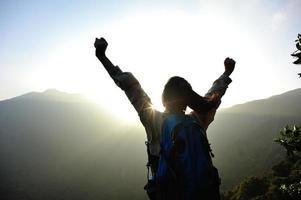 Viandante incoraggiante della donna a braccia aperte al picco di montagna foto