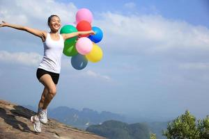 donna incoraggiante in esecuzione con palloncini colorati sul picco di montagna foto