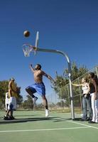 uomo che gioca a basket in campo mentre gli amici lo guardano foto