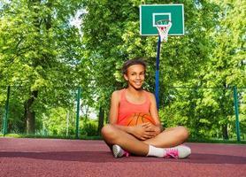 la ragazza africana sorridente si siede sul campo da giuoco con la palla foto