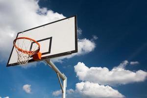 canestro da basket contro il bel cielo estivo blu con qualche soffice foto