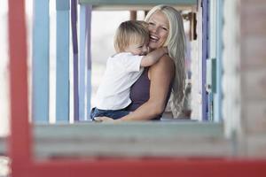 donna allegra che trasporta il figlio foto