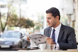il giovane uomo d'affari allegro sta riposando nella caffetteria foto