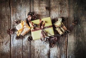 Scatole festive sul tavolo di legno decorato con pigne foto