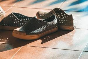 scarpe di plastica su sfondo di piastrelle con spazio di copia foto