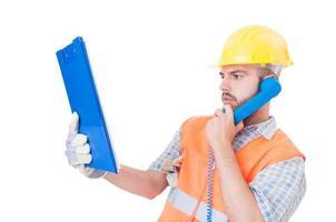 costruttore occupato che per mezzo del telefono sullo spazio bianco della copia foto