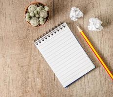 blocco note in bianco con la matita sulla tavola di legno foto
