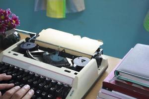 mani digitando sulla vecchia macchina da scrivere foto