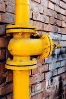 valvola del gas giallo sul muro di mattoni rossi foto