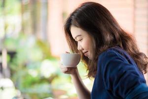 donna asiatica che si siede nella barra del caffè foto