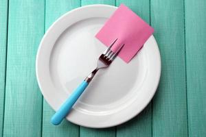 carta per appunti vuota attaccata alla forchetta, sul piatto, sul tavolo foto