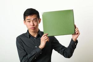 giovane uomo asiatico che mostra la scatola verde dello spazio della copia foto