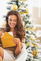 lettera di apertura felice della giovane donna vicino all'albero di Natale