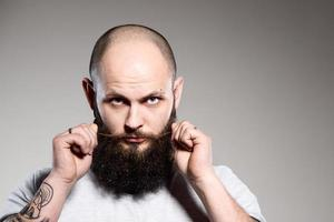uomo barbuto che tocca la barba foto