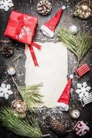 varie decorazioni natalizie intorno a un foglio di carta bianco foto