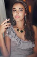 Ritratto di bella giovane donna che beve vino rosso in ristorante foto