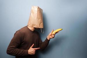 giovane con la borsa sopra la testa usando la banana come pistola foto