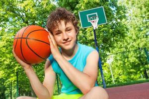 ragazzo felice si siede sul parco giochi, tiene la palla vicino al viso foto
