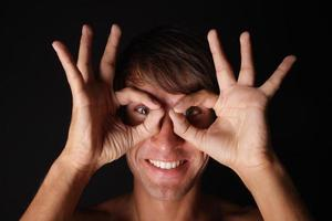 giovane uomo sorridente con gli occhiali divertenti