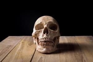 teschio umano natura morta su tavola di legno foto