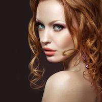 bella ragazza dai capelli rossi con trucco luminoso e riccioli.