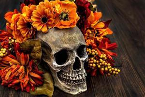teschio umano circondato da una corona di fiori autunnali. foto
