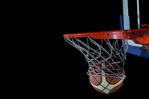 palla da basket e rete su sfondo nero foto