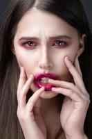 ragazza con rossetto rosa spalmato sul viso.