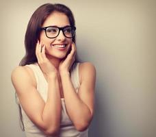 felice ridendo giovane donna casual, tenendosi per mano il viso foto