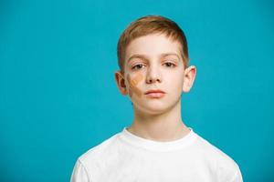 ragazzo con cerotto adesivo sulla guancia foto
