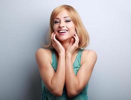 felice ridendo giovane donna bionda, tenendo la mano in faccia foto
