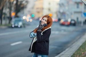 ragazza dai capelli rossi in piedi sulla strada e ridere foto