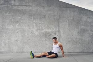 fitness atleta uomo relax e stretching muscoli e gambe foto