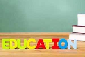 tema di educazione con libri di testo e lavagna verde