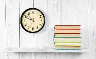 orologi e libri su una mensola in legno. foto