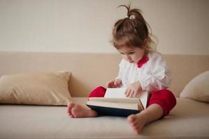 libro di lettura della bambina a casa foto